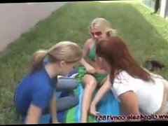 Three girls worshipping each other's feet outside