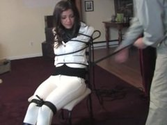 Bound brunette womanl in white suit tied to a chair
