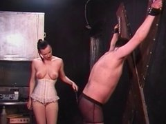 Dominatrix in white corset paddles her slave's ass in her dungeon