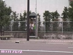 Aya presses her flat ass against some dirty phone booth glass in public
