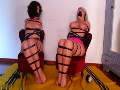 Two girls taped to chairs and toetied