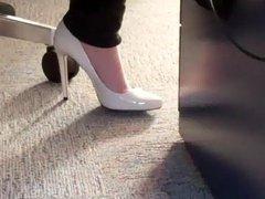dangling white high heels under desk