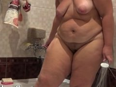 plump woman with hairy by a pussy, pissing in the bathroom