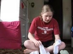 Very pretty girl puts several different pairs of white ankle socks on feet