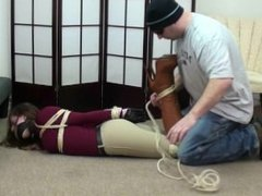 Hogtied in brown boots and riding pants