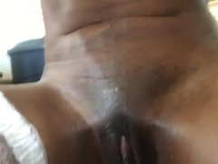 Oiled black chick dildoing her twat