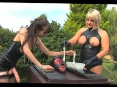 Mistresses dominate caged slave outdoors