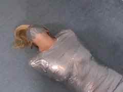 Blonde girl wrapped in duct tape struggles