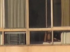 Mature woman naked in the window stretching 2