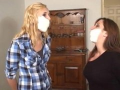 Gag fighting girls bound, mouths stuffed and microfoam taped.