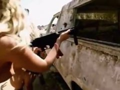 Nude women playing with guns in the desert.
