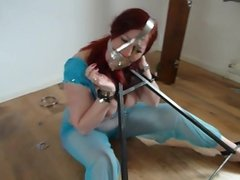 Slave in metal frame and scolds bridle