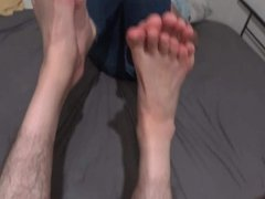 two friends playing footsies soles to soles