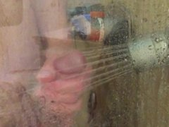 Shower head massage on penis and cum shot onto glass shower stall.