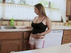 Busty brunette fucks herself with a toy in the kitchen