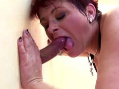Busty mature sucks and fucks two cocks at Gloryhole