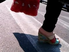 Woman with cracked heels wearing colored wedges