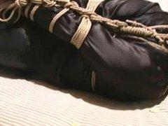 JJ tightly tied in black shiny pants