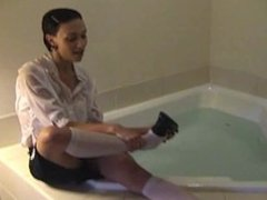 Schoolgirl takes a clothed bath