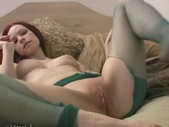 Redhead babe in green stockings masturbates with passion