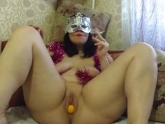 The girl in the mask smokes and plays with pussy