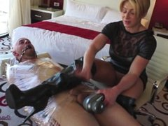 Goddess Rapture wraps up guy and gags him while rubbing feet on his cock