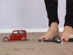 Tall brunette girl crushes a car flat under her bare feet