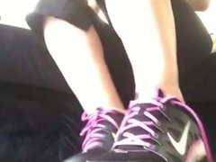 Lola takes her sneakers off to show her white socks and barefeet