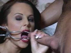 Amanda gives a handjob with a clamp holding her mouth open