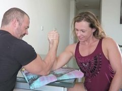 Girl measures and armwrestles with guy