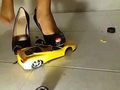 girl crushing yellow toy car