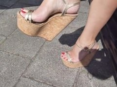 Sexy feet dangling gold wedges