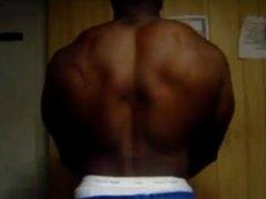 Big Black Bodybuilder Flexing Biceps in your face