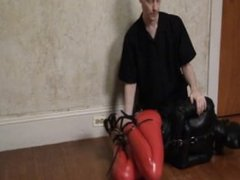 Serene Isley in red catsuit and leather hood bound and gagged