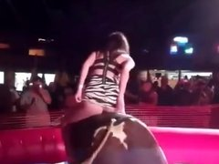 Hot girl on a mechanical bull with her dress riding up