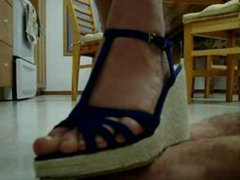 Hand trampling by beautiful feet in blue platform sandals