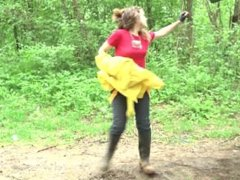 Girl wearing a red shirt and jeans gets all wet and muddy in a river
