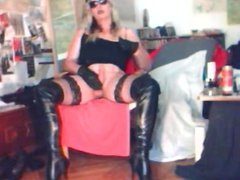 Madame Crudelitas masturbating with black pvc thigh boots. 2