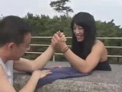 Strong asian girl flexes and armwrestles
