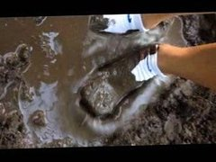Woman in nike ankle socks in mud puddle.