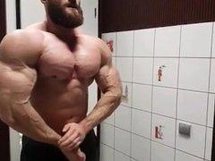 Bodybuilder Flexes Biceps in Bathroom
