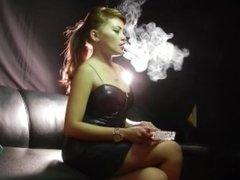 Smoking Asian in black PVC minidress