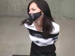 Business lady in heels taped to chair and tape gagged