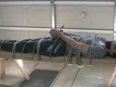Nyxon in boots, tape gagged and tied to a bench