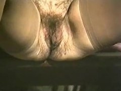 Hairy Milf Sitting on a Table and having a piss