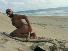 guy fucks  himself on the beach with a  wooden dildo