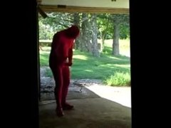 red zentai jerking off at garage door