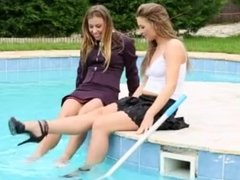 Two girls enjoy swimming in pool in clothes