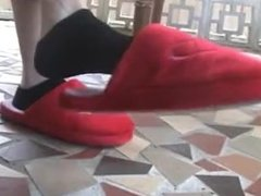 Michelle play with her feet and fuzzy red slippers