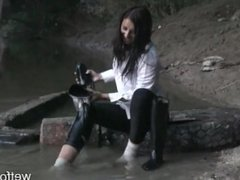 Girl in horse rider clothes get wet by the river